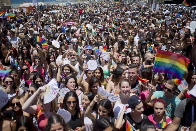 People participate the annual Gay Pride Parade in Tel Aviv, Israel, Friday, June 12, 2015. Thousands of bare-chested muscular men, drag queens in heavy makeup and high heels, women in colorful balloon costumes and others partied at Tel Aviv's annual gay pride parade on Friday, the largest event of its kind in the region. (AP Photo/Ariel Schalit)