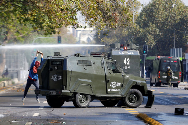 A student protester throws a stone against a riot police vehicle during a demonstration to demand changes in the education system in Santiago, Chile, April 21, 2016. (Photo by Ivan Alvarado/Reuters)