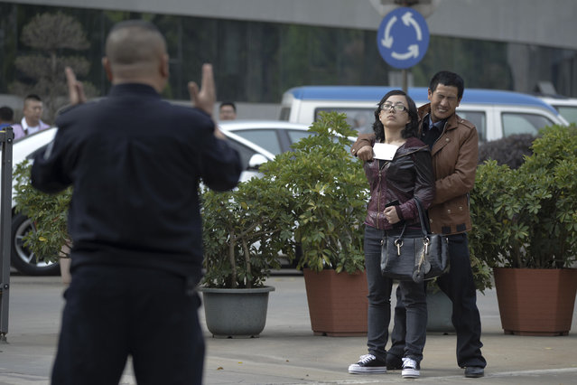 A police officer speaks to a man holding a woman hostage with a cleaver on a street in Kunming, Yunnan province April 8, 2014. Police successfully rescued the hostage and detained the man after a one-hour standoff. The reason of the crime remains unclear, local media reported. (Photo by Reuters)