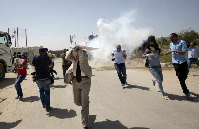 Palestinian journalists run from tear gas fired by Israeli troops during a protest calling for the release of Palestinian journalist Omar Nazzal, who was arrested by Israeli authorities over the weekend, outside Ofer military prison near the West Bank city of Ramallah, Tuesday, April 26, 2016. (Photo by Majdi Mohammed/AP Photo)