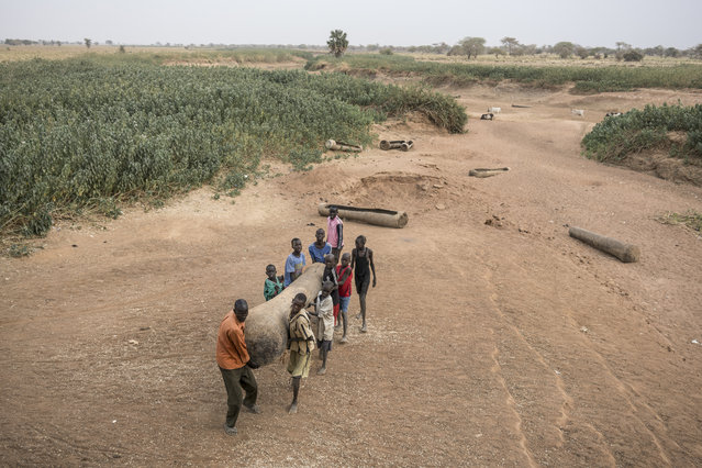 In this photo taken Sunday, March 12, 2017, children help a man move a dugout canoe from a dried-up river bed in Aweil, in South Sudan. (Photo by Mackenzie Knowles-Coursin/UNICEF via AP Photo)