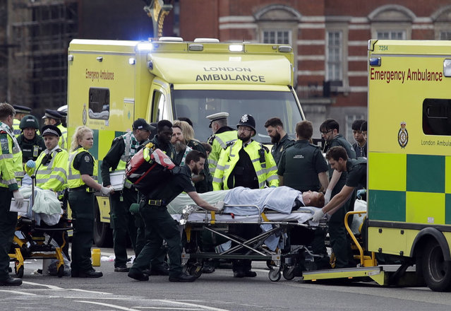 Emergency services transport an injured person to an ambulance, close to the Houses of Parliament in London, Wednesday, March 22, 2017. (Photo by Matt Dunham/AP Photo)