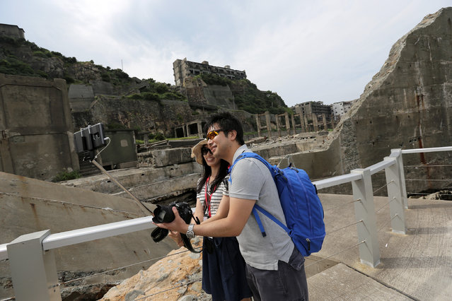 "In this June 29, 2015 photo, tourists take a selfie at Hashima Island, commonly known as Gunkanjima, which means ""Battleship Island"", off Nagasaki, Nagasaki Prefecture, southern Japan. (Photo by Eugene Hoshiko/AP Photo)"