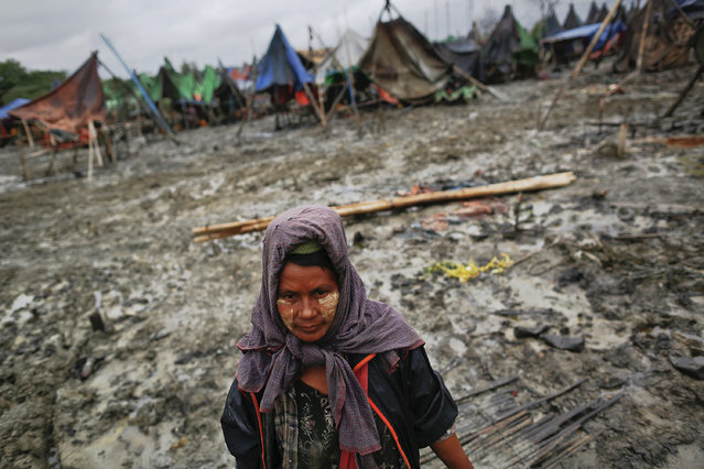 A woman walks through the mud of an oil field in the Minhla township of the Magwe district October 27, 2013. (Photo by Damir Sagolj/Reuters)
