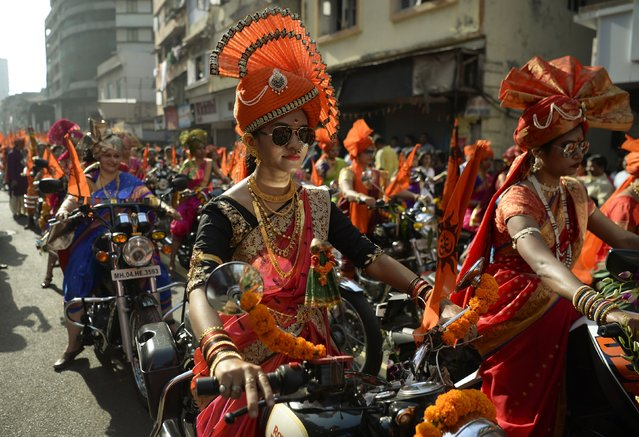 """Indian women dressed in traditional attire drive motorcycles as they take part in a procession celebrating """"Gudhi Padwa"""" or the Maharashtrian New Year in Mumbai on March 28, 2017. Gudhi Padwa is the Hindu New Year for people in India's Maharashtra state and marks the end of a harvest and the beginning of a new one. (Photo by Punit Paranjpe/AFP Photo)"""