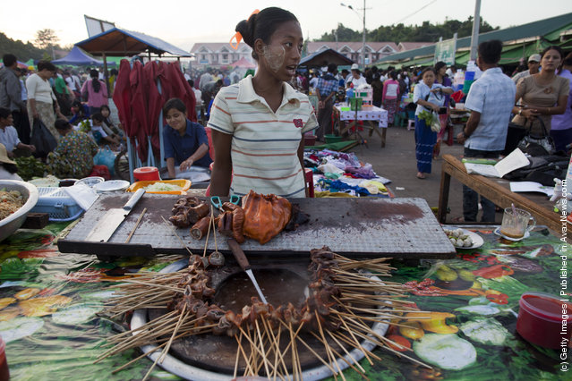 Burmese pack an afternoon market where many government workers buy fresh produce and clothing