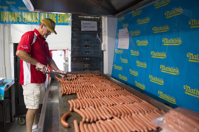 Kevin McDonald of Jackson, New Jersey prepares sausages for Nathan's Famous Hot Dog Eating Contest in Brooklyn, New York July 4, 2015. McDonald has been cooking the sausages for the contest since 1997 and averages 2,600 sausages cooked per year. (Photo by Andrew Kelly/Reuters)