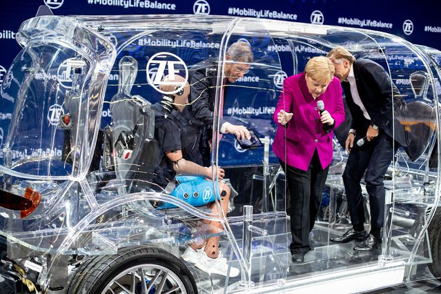 German Chancellor Angela Merkel climbs out of a transparent car with security devices during her visit to the IAA Auto Show in Frankfurt, Germany, Thursday, September 12, 2019. (Photo by Michael Probst/AP Photo)