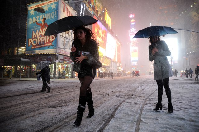 Two girls look for a taxi in the snow in Times Square in New York on February 8, 2013 during a storm affecting the northeast US. The storm was forecast to bring the heaviest snow to the densely-populated northeast corridor so far this winter, threatening power and transport links for tens of millions of people and the major cities of Boston and New York. (Photo by Mehdi Taamallah/AFP Photo)