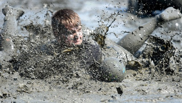 """Participants fight for the ball during a handball match at the so called """"Wattoluempiade"""" (Mud Olympics) in Brunsbuettel at the North Sea, July 11, 2015. (Photo by Fabian Bimmer/Reuters)"""