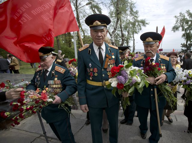 WWII veterans carry bouquets of flowers given to them by people attending Victory Day celebrations in Odessa, Ukraine, Friday, May 9, 2014. (Photo by Vadim Ghirda/AP Photo)