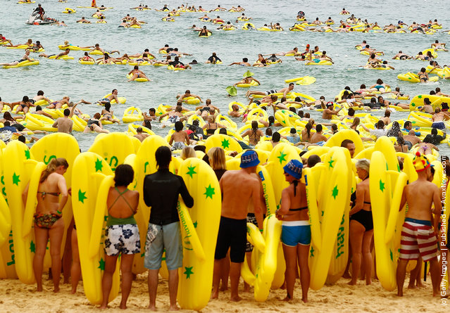 Beachgoers ride the surf on inflatable thongs ahead of the annual Havaianas Thong Challenge World Record attempt as Australia celebrates Australia Day at Bondi Beach