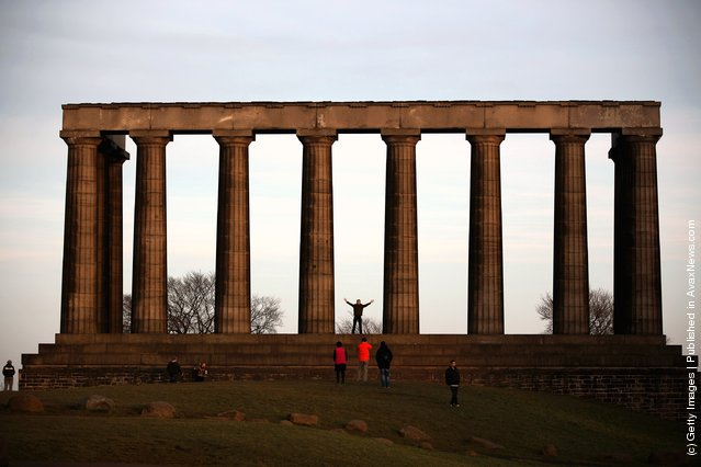 Tourists have their photographs taken at the Acropolis on Calton Hill in Edinburgh, Scotland