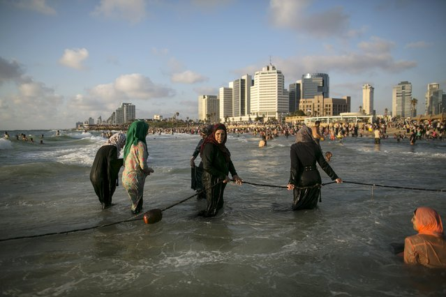 Muslim women enjoy the water of the Mediterranean sea in Tel Aviv during Eid al-Fitr, which marks the end of the holy month of Ramadan, July 19, 2015. (Photo by Baz Ratner/Reuters)