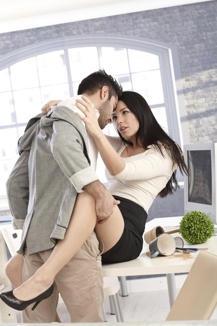 A businessman, embracing woman from behind in kitchen. (Photo by Nyul/Getty Images)