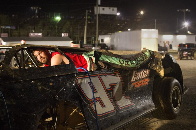 In this July 17, 2015 photo, Michael Chilton squeezes into a corner of his car to make a quick repair to some body panels after he ran into a wall during dirt track racing in the late model division at the Ponderosa Speedway in Junction City, Ky. He banged up the car in the qualifying round and had a few minutes to fix it before the final race. (Photo by David Stephenson/AP Photo)