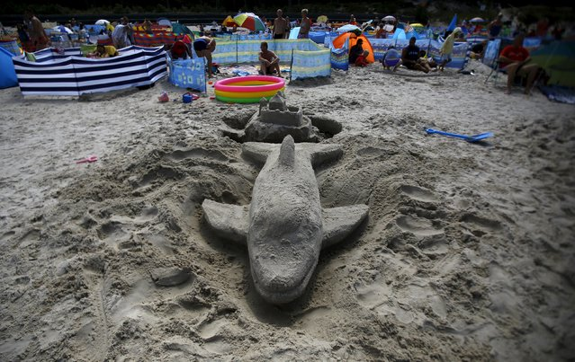 People sunbathe near sand sculptures on the beach at the Polish Baltic Sea coast  in Ostrowo, northern Poland, July 24, 2015. (Photo by Kacper Pempel/Reuters)