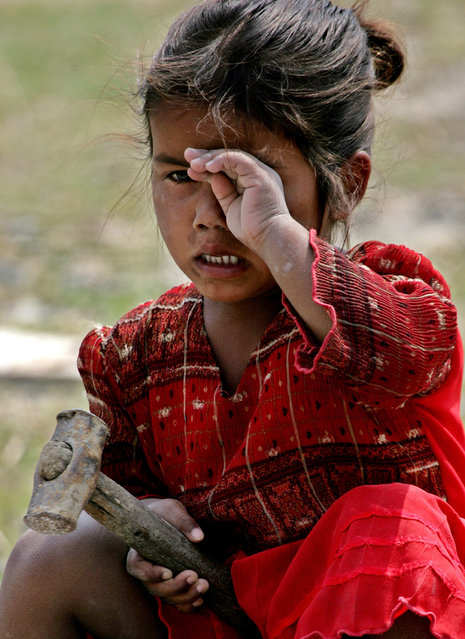 5-year-old Rina Kumari rubs her eye while cracking stones on the banks of Mahananda river in Siliguri, northeast India, March 5, 2005. Over 400 million people in India live below the internationally agreed poverty line (living on less than US $1 per day). According to estimates, several hundred thousand children work as labourers and beg on the streets in India. Photo taken on March 5, 2005. (Photo by Desmond Boylan/Reuters)