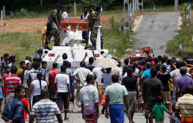 Military officials unload the landslide victim's coffins to relatives in Bulathsinhala village in Kalutara, Sri Lanka May 27, 2017. (Photo by Dinuka Liyanawatte/Reuters)