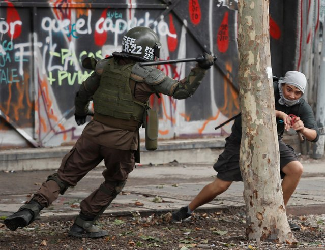 A policeman tries to hit a demonstrator during a protest against Chile's government in Santiago, Chile on December 2, 2019. (Photo by Goran Tomasevic/Reuters)
