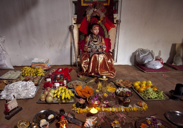 "Kumari Samita Bajracharya sits in front of devotees offers during a special puja at Kumari Ghar in Patan, Nepal, 09 April 2011. It is believed that worshipping Kumari and receiving tika from her reduces illness and avoid problems. Kumari, or Kumari Devi, is a ""living goddess"". The word literally means virgin in Nepali. The Living Goddesses are young pre-pubescent girls that are considered to be incarnations of the Hindu Goddess of Power, Kali. The Kumari retires when she reaches puberty. (Photo by Narendra Shrestha/EPA)"