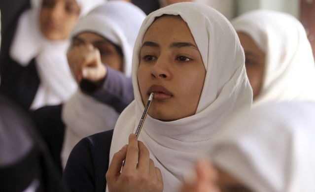 A girl puts a pencil to her lips as she listens to a teacher at a school in Yemen's capital Sanaa July 27, 2015. (Photo by Mohamed al-Sayaghi/Reuters)