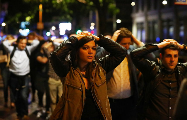 People leave the area with their hands up after an incident near London Bridge in London, Britain June 4, 2017. (Photo by Neil Hall/Reuters)