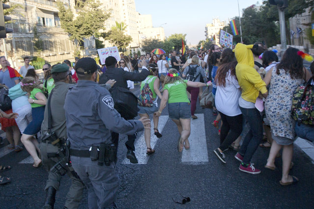 Israeli security forces reach for an ultra-Orthodox Jew attacking people with a knife during a Gay Pride parade Thursday, July 30, 2015 in central Jerusalem. (Photo by Sebastian Scheiner/AP Photo)