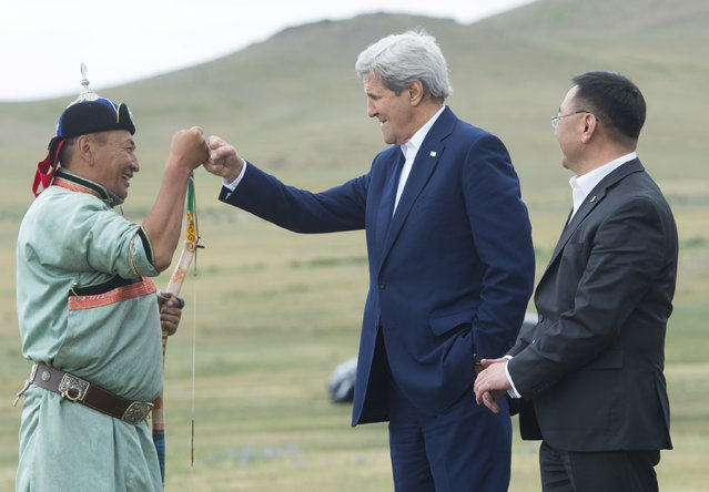 U.S. Secretary of State John Kerry fist bumps an archer alongside Mongolian Foreign Minister Lundeg Purevsuren (R) as he participates in a Naadam ceremony, a competition which traditionally includes horse racing, Mongolian wrestling and archery, in Ulan Bator, Mongolia, June 5, 2016. (Photo by Saul Loeb/Reuters)