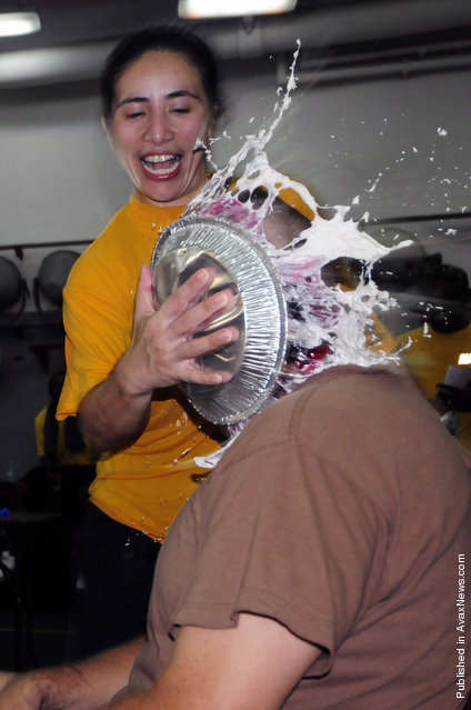 Ensign Patricia Cunanan shoves a pie in the face of Command Master Chief Michael Lucas during a fundraiser aboard the amphibious dock landing ship USS Comstock (LSD 45)