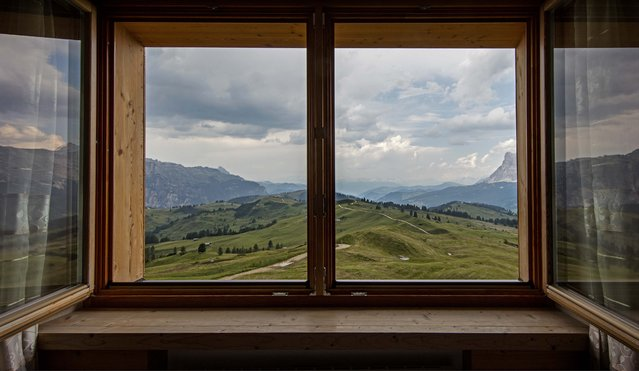 The rolling hills and Dolomite Mountains are seen from a room at the Rifugio Prolongia near Corvara in northern Italy July 17, 2015. (Photo by Bob Strong/Reuters)