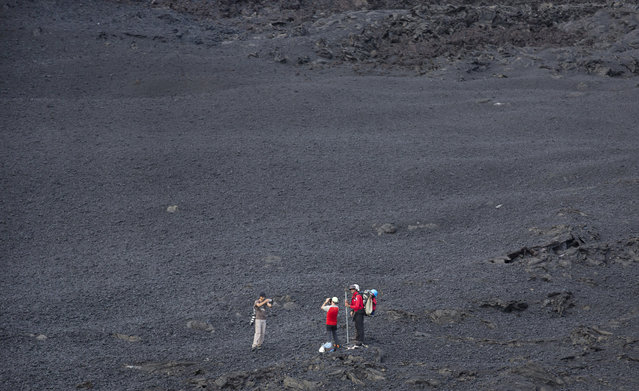 "Volcanologists take photographs of themselves and the volcano as they stand in a field of cooled volcanic rock, as lava erupts nearby from the Piton de la Fournaise ""Peak of the Furnace"" volcano, on the southeastern corner of the Indian Ocean island of Reunion Saturday, August 1, 2015. (Photo by Ben Curtis/AP Photo)"