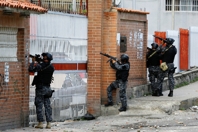Venezuelan national guards point their weapons towards a building after a protest over food shortage and against Venezuela's government in Caracas, Venezuela, June 10, 2016. (Photo by Ivan Alvarado/Reuters)