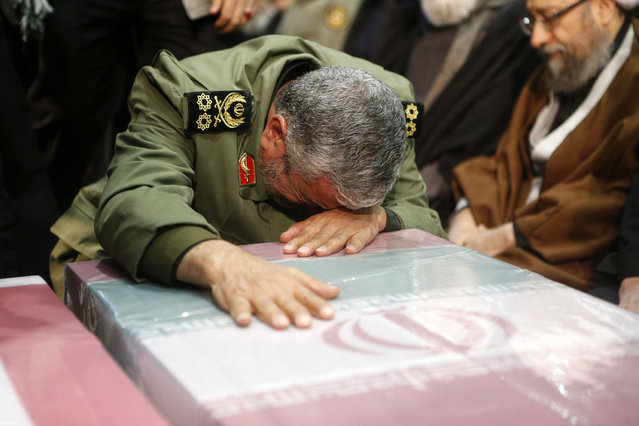 A handout picture provided by the office of Iran's Supreme Leader Ayatollah Ali Khamenei shows an unidentified Revolutianary Guard commander paying over the caskets of slain Iranian military commander Qasem Soleimani during a funeral ceremony at Tehran University in the Iranian capital on January 6, 2020. Mourners packed the streets of Tehran for ceremonies to pay homage to Soleimani, who spearheaded Iran's Middle East operations as commander of the Revolutionary Guards' Quds Force and was killed in a US drone strike on January 3 near Baghdad airport. (Photo by Iranian Supreme Leader's Website/AFP Photo)