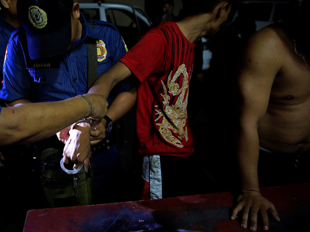 """A member of the Philippine National Police handcuffs a man after he tried to escape detention during the """"Rid the Streets of Drinkers and Youth"""" operation in Las Pinas city, metro Manila, Philippines June 1, 2016. (Photo by Romeo Ranoco/Reuters)"""