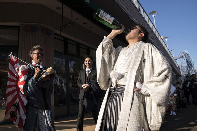 A man drinks a bottle of sake after attending a Coming of Age ceremony at the Toshimaen amusement park on January 13, 2020 in Tokyo, Japan. (Photo by Tomohiro Ohsumi/Getty Images)