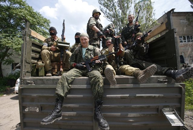 """Pro-Russian separatist fighters from the so-called Battalion """"Vostok"""" (East) sit in a truck as they set out from a base in the eastern Ukrainian city of Donetsk, July 10, 2014. Ukrainian forces regained more ground but sustained further casualties on Thursday in clashes with separatists, while two Western allies urged Russia's Vladimir Putin to exert more pressure on the rebels to find a negotiated end to the conflict. (Photo by Maxim Zmeyev/Reuters)"""