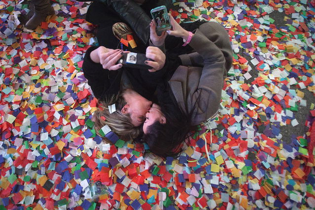 Lindsay Mann (L) and Anabella Mowbray kiss as they take photos of themselves laying in the confetti on 7th Avenue in Times Square on New Year's Eve in New York January 1, 2015. (Photo by Carlo Allegri/Reuters)