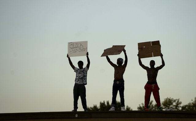 Protesters hold up signs on top of a closed business in Ferguson, Missouri, August 10, 2015. (Photo by Rick Wilking/Reuters)