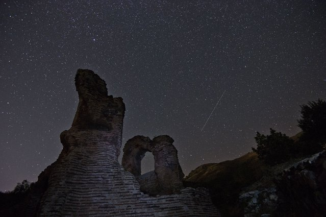A long exposure image showing a Perseids meteor (R) streaking across the night sky over the remains of St. Ilia Roman early Christian basilica dated back to the 5th6th century AD near the town of Pirdop, early on August 12, 2015. The Perseid meteor shower occurs every year in August when the Earth passes through the debris and dust of the Swift-Tuttle comet. (Photo by Nikolay Doychinov/AFP Photo)