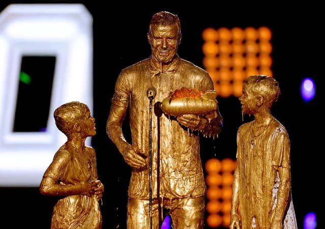 Soccer player David Beckham (C) with Cruz Beckham (L) and Romeo Beckham (R) get slimed onstage during Nickelodeon Kids' Choice Sports Awards 2014 at UCLA's Pauley Pavilion on July 17, 2014 in Los Angeles, California. (Photo by Kevin Winter/Getty Images)