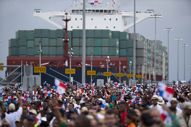 Thousands of spectators watch as the Neopanamax cargo ship, Cosco Shipping Panama, makes its way through the new new Agua Clara locks, part of the Panama Canal expansion project, near the port city of Colon, Panama, Sunday June 26, 2016. The ship carrying more than 9,000 containers entered the newly expanded locks that will double the Panama Canal's capacity in a multibillion-dollar bet on a bright economic future despite tough times for international shipping. (Photo by Moises Castillo/AP Photo)