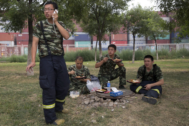 Chinese firefighter eat lunch as they wait to be activated near the site of an explosion in northeastern China's Tianjin municipality Saturday, August 15, 2015. (Photo by Ng Han Guan/AP Photo)