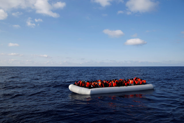 Migrants in a dinghy await rescue by the Migrant Offshore Aid Station (MOAS), around 20 nautical miles off the coast of Libya, June 23, 2016. (Photo by Darrin Zammit Lupi/Reuters)