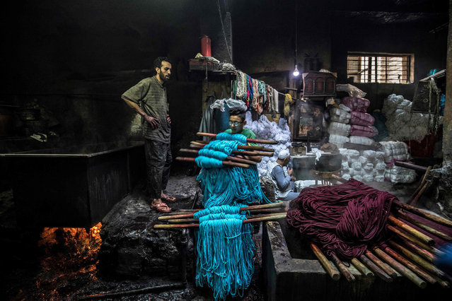 A workers carries away dyed yarns at a traditional hand-dying workshop in the Egyptian capital Cairo's centuries old district of Darb al-Ahmar on January 21, 2020. In Cairo's centuries-old Darb al-Ahmar district, Salama Mahmoud Salama's dye workshop is a multi-coloured den of textiles and busy workers colouring all kinds of fabrics. Salama and his relatives lay out the long, flowing threads, which will be used for everything from handmade shoes to rugs and drapes, and dip them in huge, piping-hot colour baths – no gloves or masks protecting them from the dyes and chemical fumes. The workshop in Islamic Cairo has been going strong for over a hundred years. (Photo by Khaled Desouki/AFP Photo)