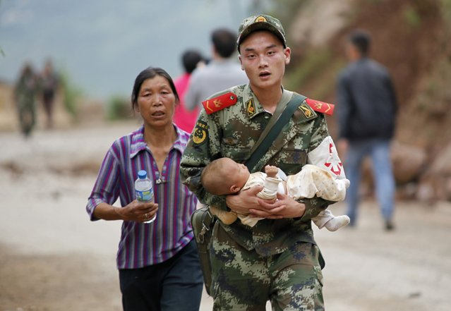 A paramilitary policeman carries a baby in his arms after an earthquake hit Ludian county of Zhaotong, Yunnan province August 3, 2014. The magnitude 6.5 earthquake struck southwestern China on Sunday, killing at least 175 people and leaving more than 180 missing and 1,400 injured in the remote area of Yunnan province, causing thousands of buildings, including a school, to collapse, Xinhua News Agency reported. (Photo by Reuters/China Daily)