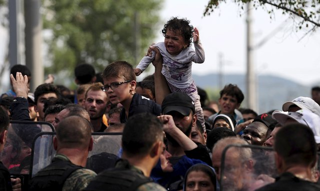 A baby cries at the border line dividing Macedonia and Greece August 21, 2015. (Photo by Ognen Teofilovski/Reuters)