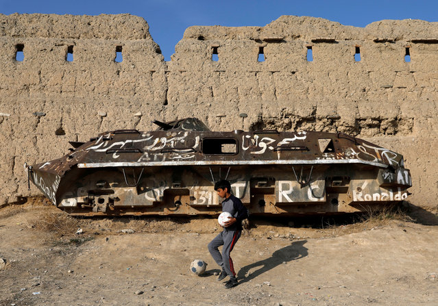 An Afghan boy walks past a destroyed Russian-made tank, in Kabul, Afghanistan on February 24, 2020. (Photo by Mohammad Ismail/Reuters)
