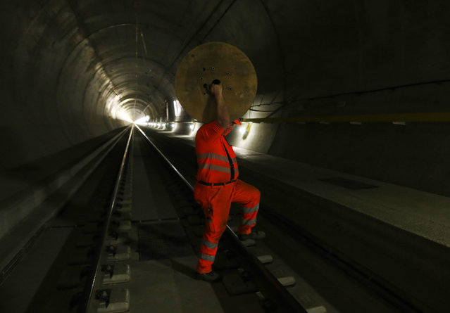 A worker carries material over the railway tracks in the NEAT Gotthard Base tunnel near Amsteg September 3, 2014. (Photo by Ruben Sprich/Reuters)