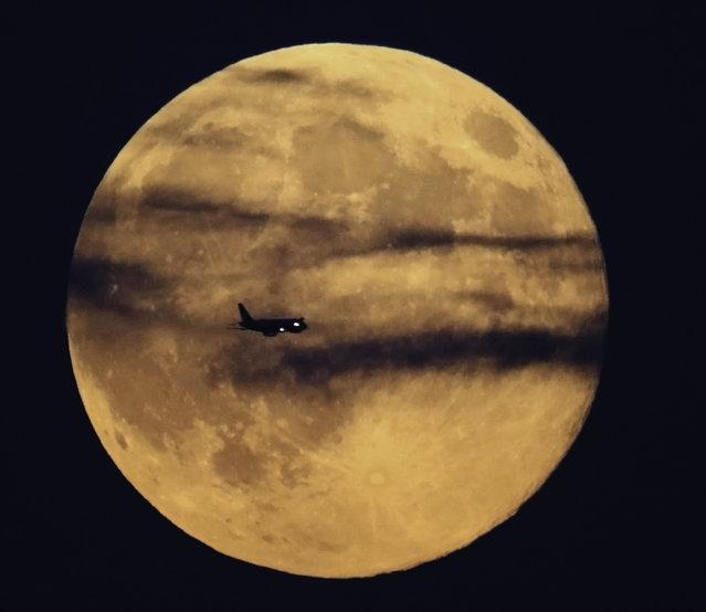 Tonight's full Supermoon is seen over Boston, as a jet flies through it. (Photo by Mark Edwards/Splash News)